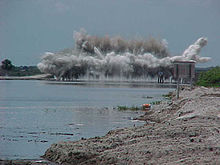 A color photograph of a large cement structure on the C-38 Canal being destroyed with explosives