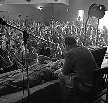 A mostly seated crowd watches as Hubbard, seated on a chair, speaks to a woman lying prone in front of him.