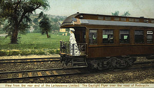 Phoebe Snow (character) - 1906 postcard promotion for the Lackawanna Limited - Phoebe Snow stands on the observation car platform dressed in white and holding her traditional violet corsage
