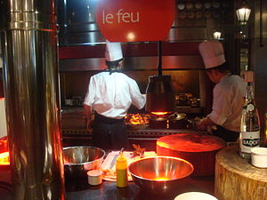 Flattop grill - A flattop grill and fireplace area atop the grill used to heat an above cooking area, at Le Feu restaurant in Lyon, France