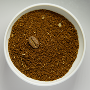Less coarsely grounded coffee beans in white bowl with intact roasted bean.png