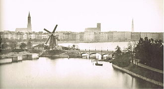 Picture clock with Alster panorama - Photograph from 1860 showing the windmill, lake and original bridge, from approximately the same orientation as the painting