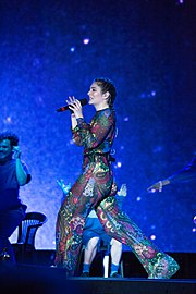 Lorde looks sideways as she performs onstage in a sheer coloured outfit.
