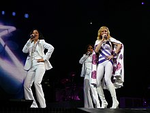 A blond woman, wearing a white leotard with purple stripes and white cape, singing on a stage. She is flanked by two female singer in white tuxedos. In the background the animation of a star can be seen.