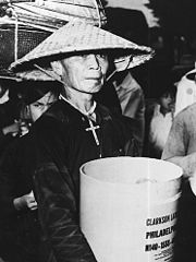 Wrinkled old man wearing a straw conical hat, black ao baba, and a large crucifix necklace holds a white cylindrical container with English language writing on it. Behind him is another person, partially obscured, wearing black with straw baskets of luggage on their head.