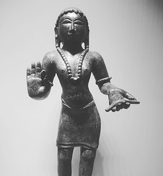 "Manikkavacakar - Manikkavachakar statue in tribhanga holding Palm leaf written ""Om Namah Shivaya"" in Tamizh script on it. Statue is in AP State Archeological Museum."