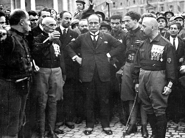 Benito Mussolini with three of the four quadrumvirs during the March on Rome (from left to right: unknown, de Bono, Mussolini, Balbo and de Vecchi) March on Rome.jpg