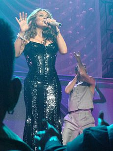 A woman wearing black ensemble, performing in a concert.