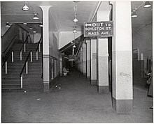 "A subway platform with an overhead sign reading ""Out to Boylston St. and Mass Ave."
