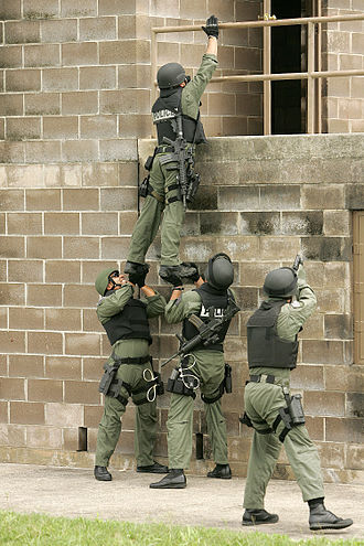SWAT - U.S. Air Force 37th Training Wing's Emergency Services Team use a team lift technique to enter a target building during training at Lackland Air Force Base, Texas on April 24, 2007.