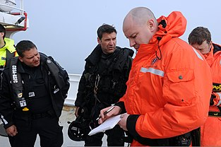 CBSA and RCMP members share information on the survey research vessel Strait Hunter, simulating a migrant vessel, during Frontier Sentinel (2012)