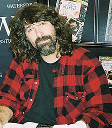 A male with medium-length hair and a goatee, wearing a red-and-black plaid buttoned shirt on top of a black t-shirt poses at an autograph signing.