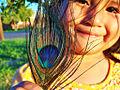 Monie with a peacock feather - Tohono Oodham - Cheryl Maze Walker - Flickr - USDAgov.jpg