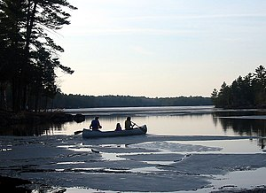 A group of girls setting off in a canoe on a l...