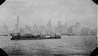 Car float -  A railroad car float in the Upper New York Bay, 1919. A tugboat (towboat) stack is visible behind the middle car.