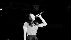 A black-and-white image. Against a black background, a young woman in side profile holds a microphone high and belts into it.