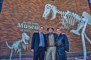 Brown County, Wisconsin - The County Executive Troy Streckenbach, Brown County Neville Museum Director, and Mayor Jim Schmitt of Green Bay in front of the dinosaur sculpture.