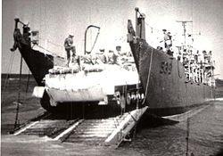 """אח""""י קיסריה (פ-53) מעמיסה נגמ""""ש בחוף המצרי במהלך מבצע רביב."""