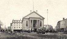 Black and white photo of a grand Greek revival civic building with a gable roof, an oversized portico supported by four large ionic columns flanked to the left and right by tall, barrel arch windows, below a simple pediment. The building has a public open space paved with dirt and granite pavers and crossed by streetcar tracks in front of it. The building is surrounded by nineteenth century mixed use urban buildings, mostly of brick and granite. There are multiple people and horse-drawn carts in the public space.