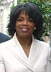A woman with short wavy hair smiles, and is wearing a white jacket.
