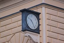 A clock stopped at 10:25 located outside of Bologna Centrale railway station.
