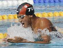 Brown skinned man wearing goggles and a cap with the black and red colours of his country and the flag of Tunisia, wearing a swimsuit not covering his torso, does breaststroke, with his arms parallel to the surface of the water. He is opening his mouth to take in a breath as his head is above the water.