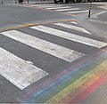 Zebra crossing with rainbow stripes running perpendiculary along its sides.