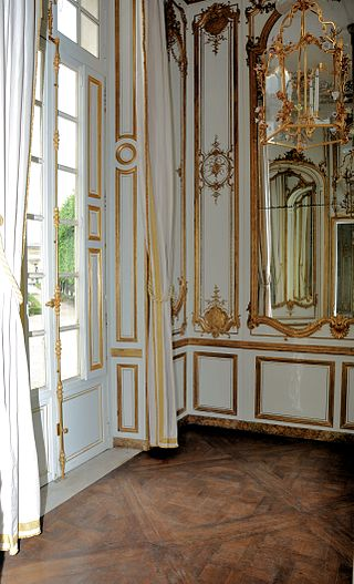 Vue du boudoir depuis le salon central montrant les miroirs dorés et le parquet Versailles.