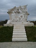 White stone memorial, with steps and people escaping