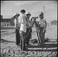 Poston, Arizona. Evacuees of Japanese ancestry watch fellow evacuee surveyors at work at this War R . . . - NARA - 538566.tif