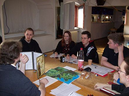 A group playing a tabletop RPG. The GM is at left using a cardboard screen to hide dice rolls from the players. RPG-2009-Berlin-2.jpg
