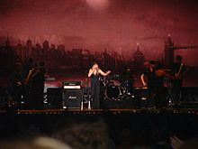 Faraway image of a blond woman singing in front of a London backdrop and in front of an acoustic band. She is wearing a black strapless blouse with matching pants and matching hat. She's singing to a microphone, which she is holding with her left arm.