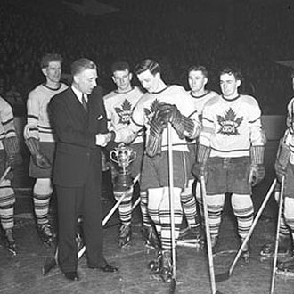 Red Dutton - Dutton (left front) presents the Calder Memorial Trophy to Gus Bodnar as NHL president in 1944