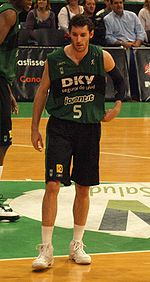 A basketball player, wearing a green-black jersey with the word «DKV JOVENTUT» and the number 5 on the front, stands on a basketball court.
