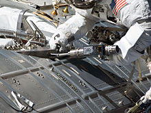 An astronaut uses a screwdriver to activate a docking port on an ISS module.