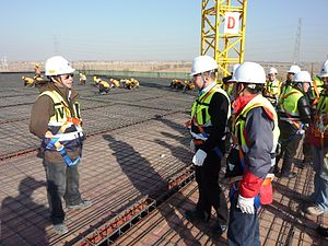 Personal protective equipment - Safety equipment and supervisor instructions at a construction site