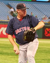 Boston pitcher, in black hat, navy blue top and grey pants, delivering a practice pitch for the Red Sox the day before a game. Nearly empty bleachers are visible behind him.