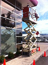 a scissor lift aerial work platform is being used to access high windows - Window Cleaner Job Description