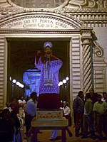 A statue of St. Peter placed on a pedestal in front of an entrance to the church. The facade of the church and inside is lit up and people are standing around the statue.