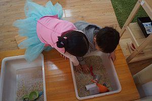 Qingdao Amerasia International School - Montessori Toddler students practice their sensory skills with a sandbox