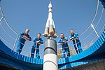 Soyuz MS-10 crew and backup crew at the Soyuz rocket monument behind the Cosmonaut Hotel.jpg