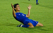 Chhetri on his knees in a blue football shirt and blue football shorts. His arms are outstretched and he is smiling after just scoring a goal.