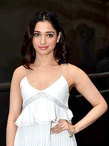 Tamannaah dressed in a white shirt and looking at the camera