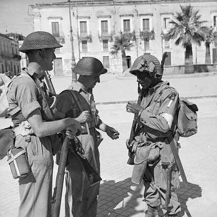 British troops of the 6th Battalion, Durham Light Infantry, part of the British 50th Division, with an American paratrooper of the 505th Parachute Infantry Regiment, part of the U.S. 82nd Airborne Division, in Avola, 11 July 1943. The British Army in Sicily 1943 NA4614.jpg