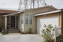 A bungalow with an attached garage with a tower and power lines in the background