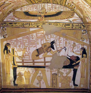 Fresco of a mummy lying on a bier. Women stand at the head and foot of the bier, while a winged woman kneels in the register above