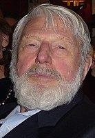A headshot of a caucasian man with grey hair and a bushy grey beard.