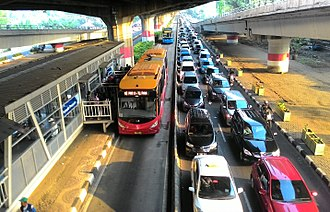 TransJakarta - TransJakarta bus on the dedicated bus lane separated from heavy traffic