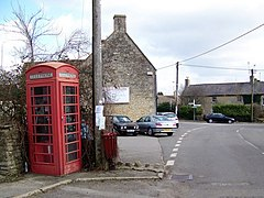 Street scene. Red telephone box and telegraph pole. Stone buildings around road junction.