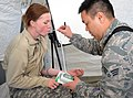 U.S. Air Force Senior Airman Charlie Phu, right, gets vital sign readings from Army Pfc. Jessica Lammert, both assigned to the Chemical, Biological, Radiological, Nuclear and high-yield Explosives Enhanced 140327-Z-CH590-280.jpg